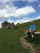 Abandoned stone barn, happy hiker at rest